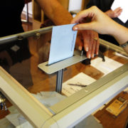 Hand inserts vote into ballot box