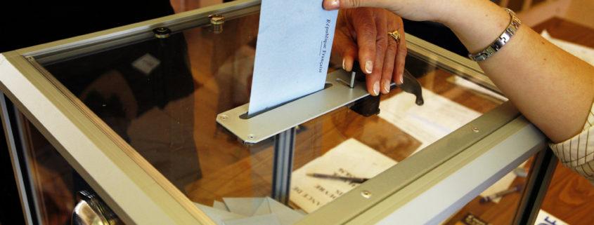 Hand inserts vote into ballot box
